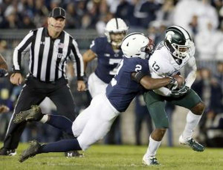 Penn State's Donovan Johnson (2) tackles Michigan State's Laress Nelson (13) after a catch during the second half of an NCAA college football game in State College, Pa., Saturday. (AP Photo/Chris Knight)