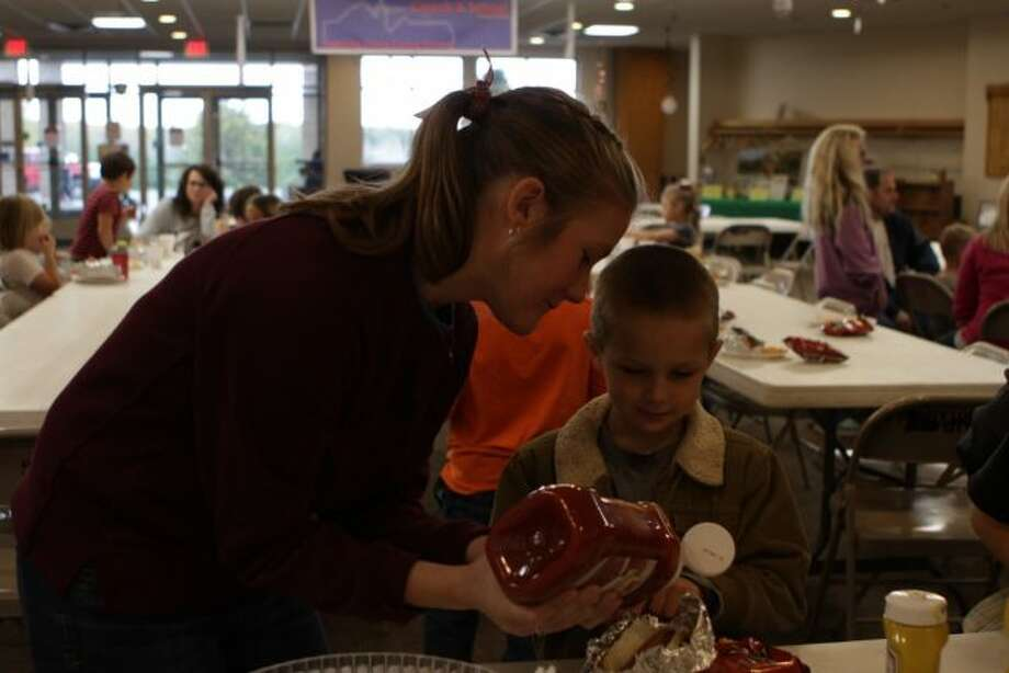 During a tailgate luncheon at Trinity Lutheran School, news first- and second-grade teacher Emma Eising (left) helps one of her students, Benjamin Visner, prepare his food. (Pioneer photo/Meghan Gunther-Haas)
