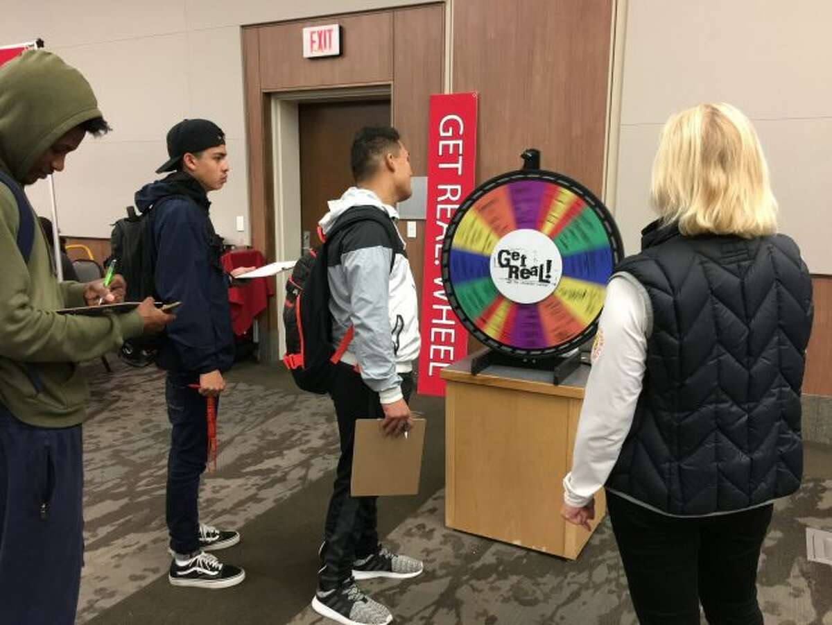 Get Real, an interactive personal finance exploration game developed by Ferris State University's Office of Scholarships and Financial Aid, was offered on Wednesday. Pictured, students spin a wheel to see how the results will impact their lives in the game. Results ranged from detrimental - like a driving while impaired arrest or divorce - to beneficial - such as a high credit score. (Courtesy photo)