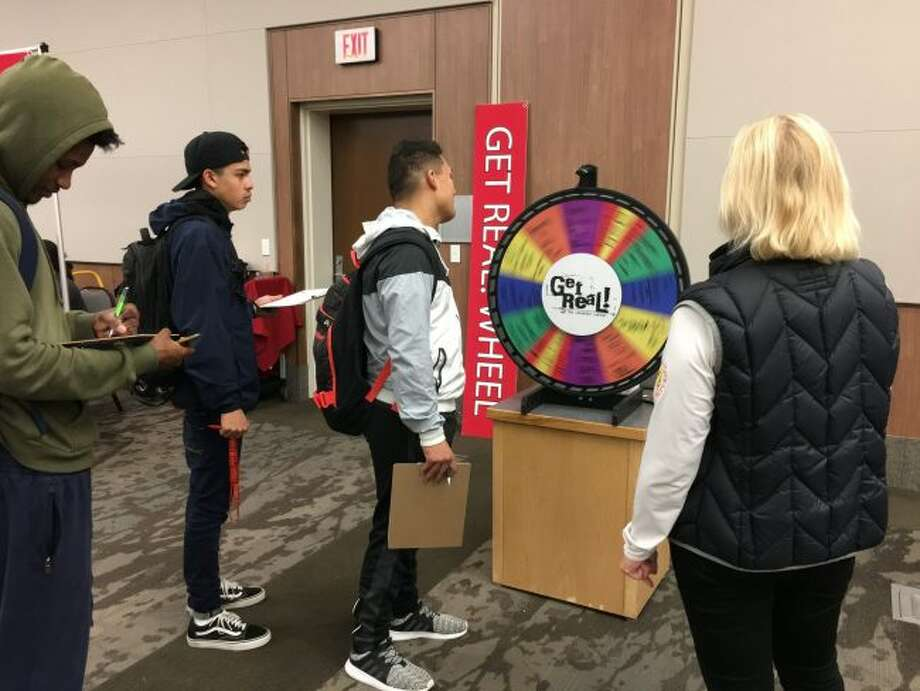 Get Real, an interactive personal finance exploration game developed by Ferris State University's Office of Scholarships and Financial Aid, was offered on Wednesday. Pictured, students spin a wheel to see how the results will impact their lives in the game. Results ranged from detrimental — like a driving while impaired arrest or divorce — to beneficial — such as a high credit score. (Courtesy photo)