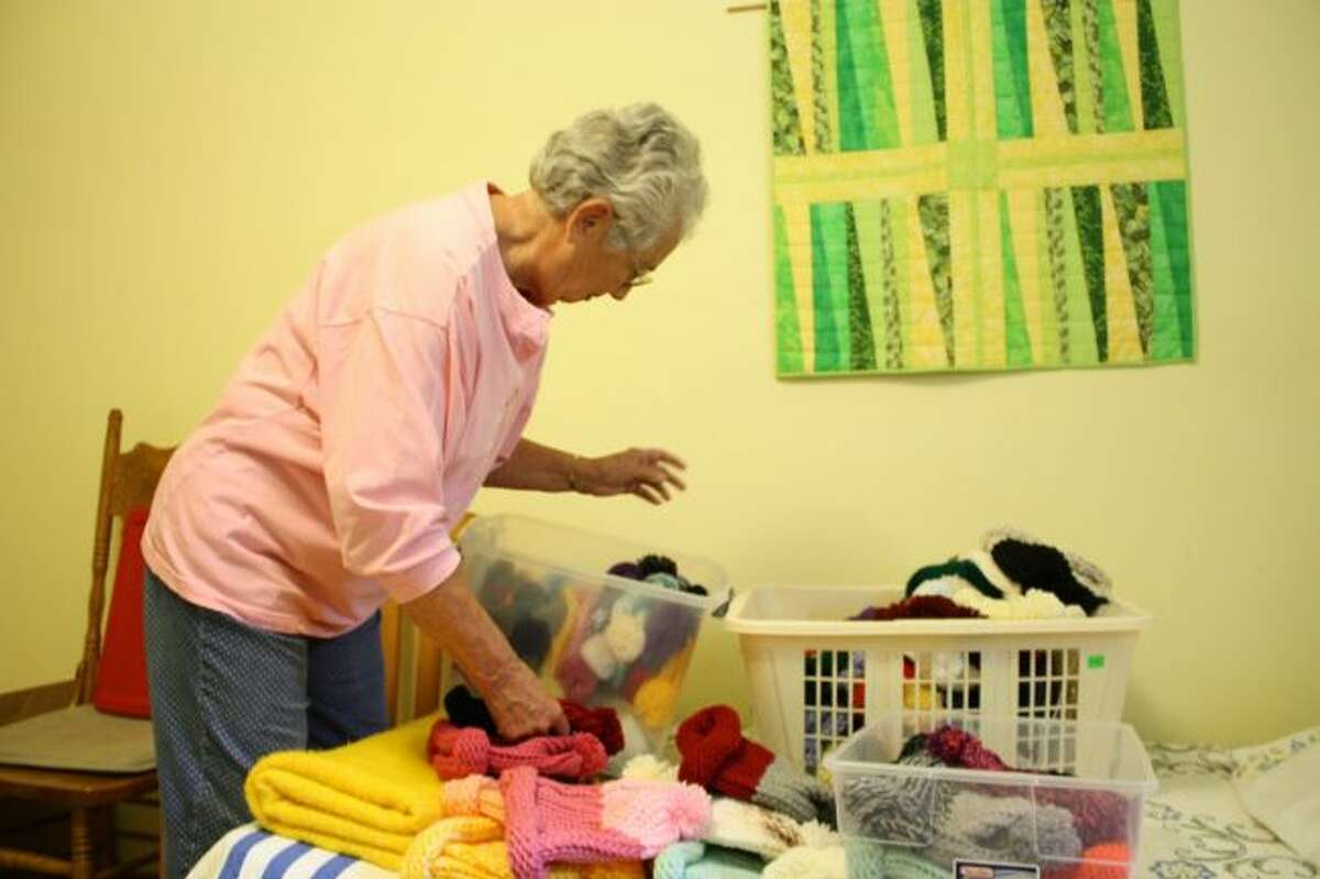 Sara Ham sorts through the more than 70 hats she has on hand to give to the Manna Pantry for distribution this year. (Pioneer photo/Candy Allan)