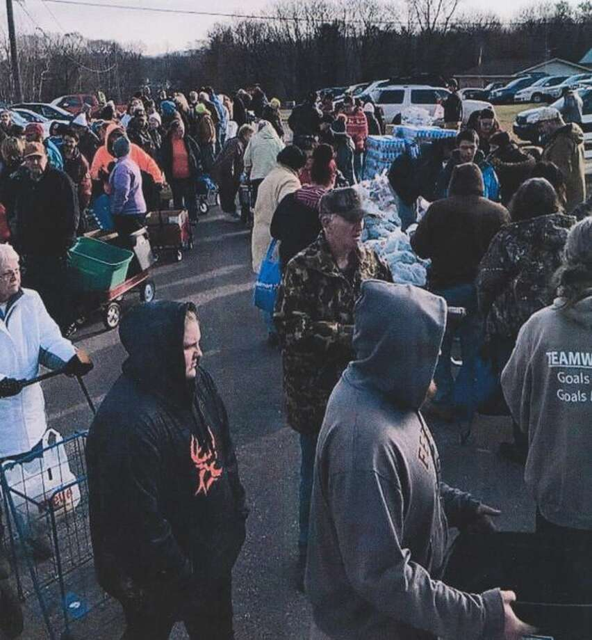 Area residents in line to receive food (left side of photo) wait their turn to go through the distribution line (right side of photo) during a distribution day in 2017 at Paris United Methodist Church. (Courtesy photo)