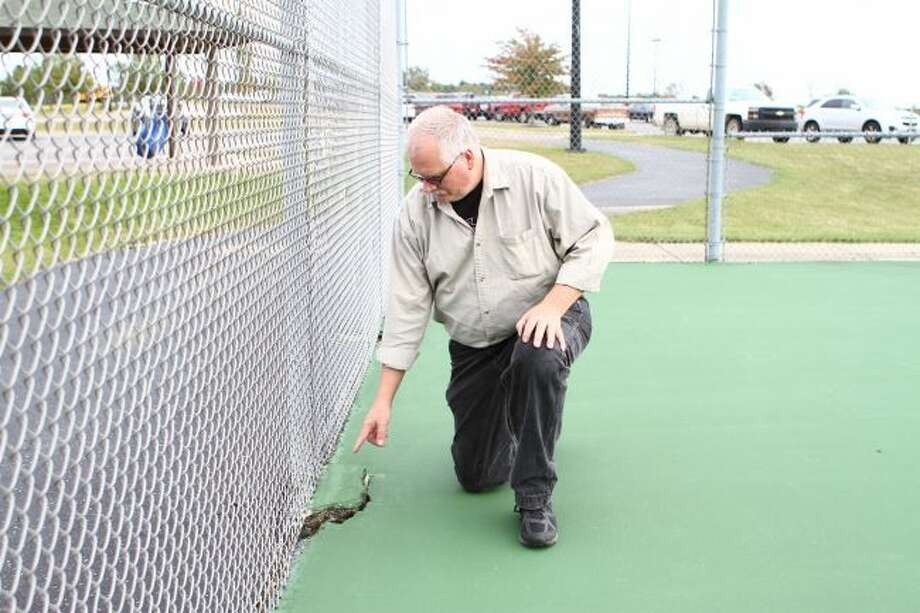 Big Rapids Public Schools Facilities Director Bill Fogel indicates a large crack on the tennis courts behind the high school. One of the focal points of the proposed bond is improving infrastructure such as on the court. (Pioneer File Photo)