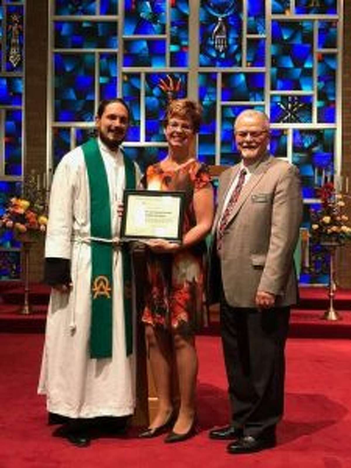 St. Peter's Lutheran School recently was awarded national accreditation. (Pictured) Zonna Heck, interim principal and kindergarten teacher, holds the accreditation award alongside Pastor Johnathon Williams (left) and Assistant Superintendent of Michigan Lutheran Schools Chuck Winterstein (right). (Courtesy photo)