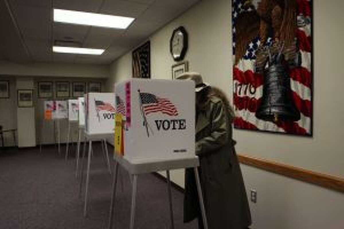 CASTING A BALLOT: City Commissioner Lynn Anderson votes in one of the booths set up at City Hall.