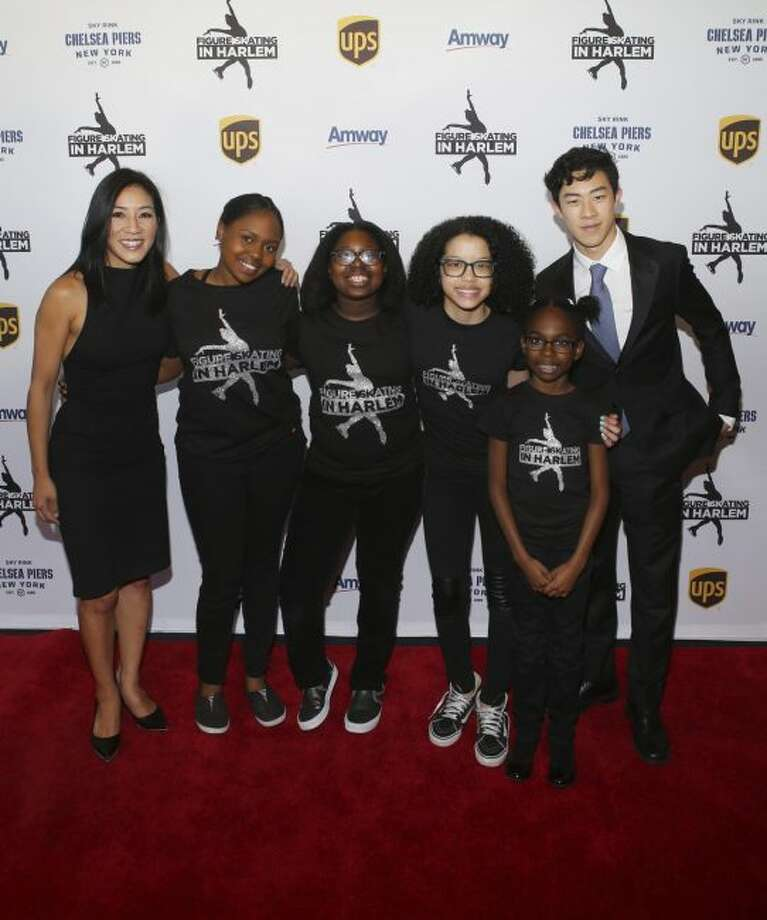 In this image taken Monday, May 1, 2018, and provided by Figure Skating in Harlem, figure skaters Michelle Kwan, left, and Nathan Chen, right, pose with members of Figure Skaters in Harlem at Chelsea Piers in New York. (Udo Salters Photography/Figure Skating in Harlem via AP)