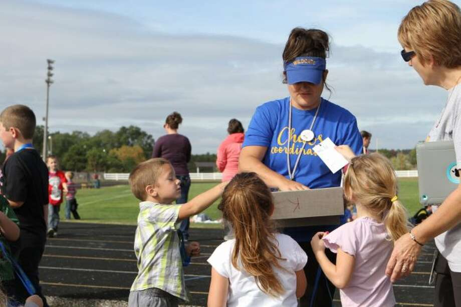 Evart Elementary students hand in cards, which were marked for each time the pupil raced around the track during the Wildcat Walk in October. The walk is one of the many events organized by members of the Parents for Kids (PFK) throughout the school year. (Pioneer file photos)