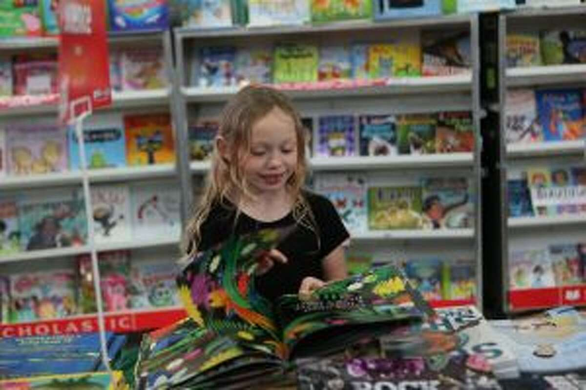 Across Mecosta and Osceola counties, parent-teacher organizations help in the schools in a variety of ways, including hosting book fairs. (Pictured) A student flips through a story displayed during a book fair in March at Riverview Elementary School.