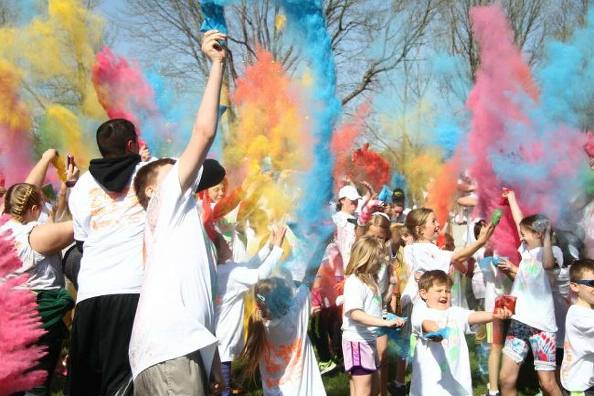 Colorful dye is flung into the air at the end of the Coyote Color Run on Saturday at Westerburg Park. (Pioneer photos/Emily Grove)