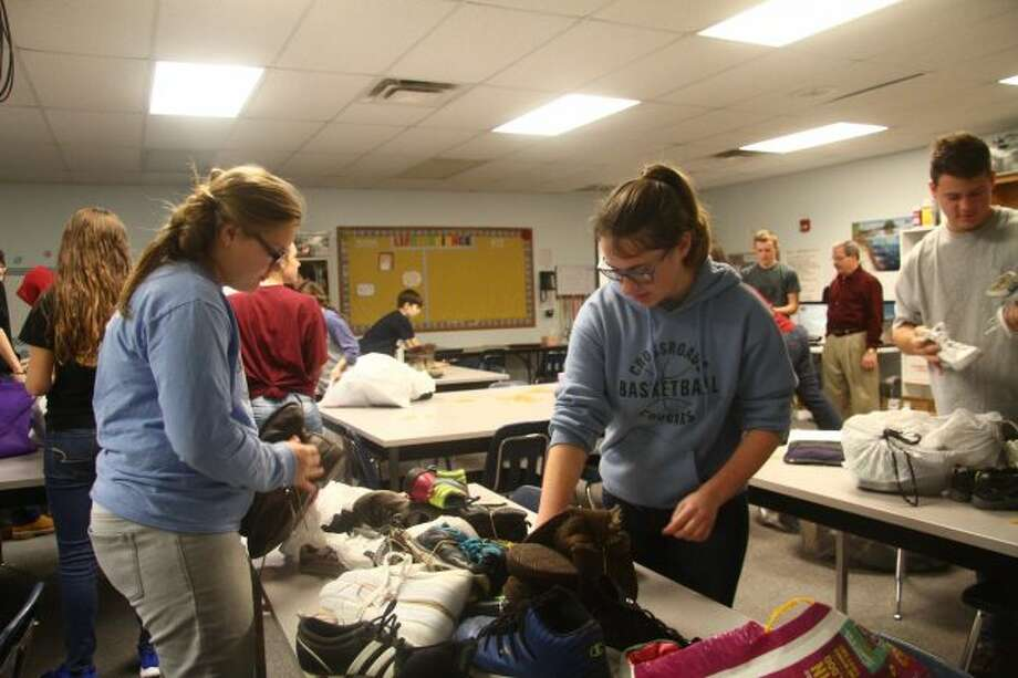 CCA students at a previous shoe drive organize the shoes they collected. This year, the shoe drive will run until Dec. 1. (Pioneer file photo)