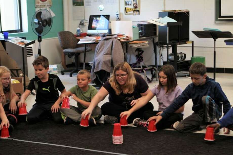 """During a Halloween-themed lesson, the new Morley Stanwood Elementary School music teacher, Amanda McCarty (center), teaches students how to keep the rhythm for the theme song of """"The Addams Family,"""" using just their hands, the floor and a plastic cup. (Pioneer photo/Meghan Gunther-Haas)"""