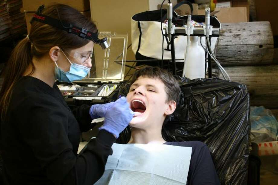 A traveling dental hygienist works on a student's teeth during a mobile dental clinic at Morley Stanwood Community Schools in 2016. A bill recently passed in the Michigan Senate would create a mid-level dental provider, a dental therapist, which is similar to a nurse practitioner in the medical field. (Pioneer file photo)