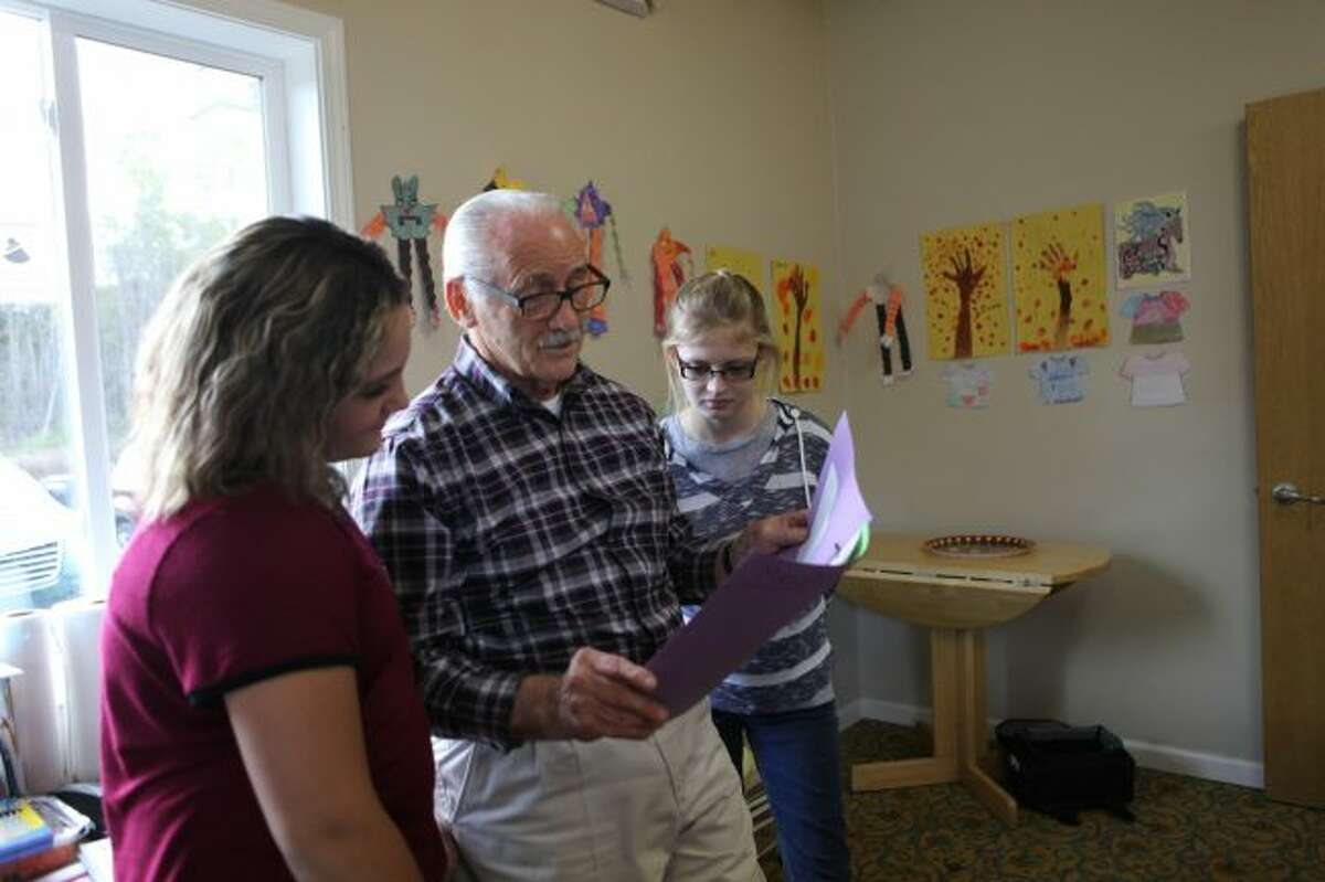 James Shaw, who directed the Mecosta County Youth and Family Center with his wife, Bonnie, looks over a student's homework. Now under the director of Stacey Knoertzer, who has 25 years of after-school programming experience, a new millage is sought to continue the growth of the center. (Pioneer file photo)