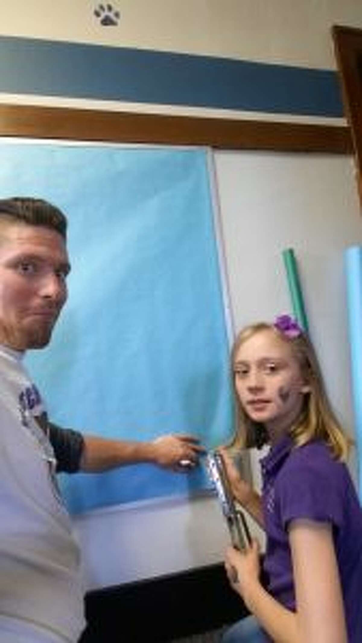 HELPING HAND: McNally works with his daughter, Zoe, putting a new background on one of the hallway bulletin boards.