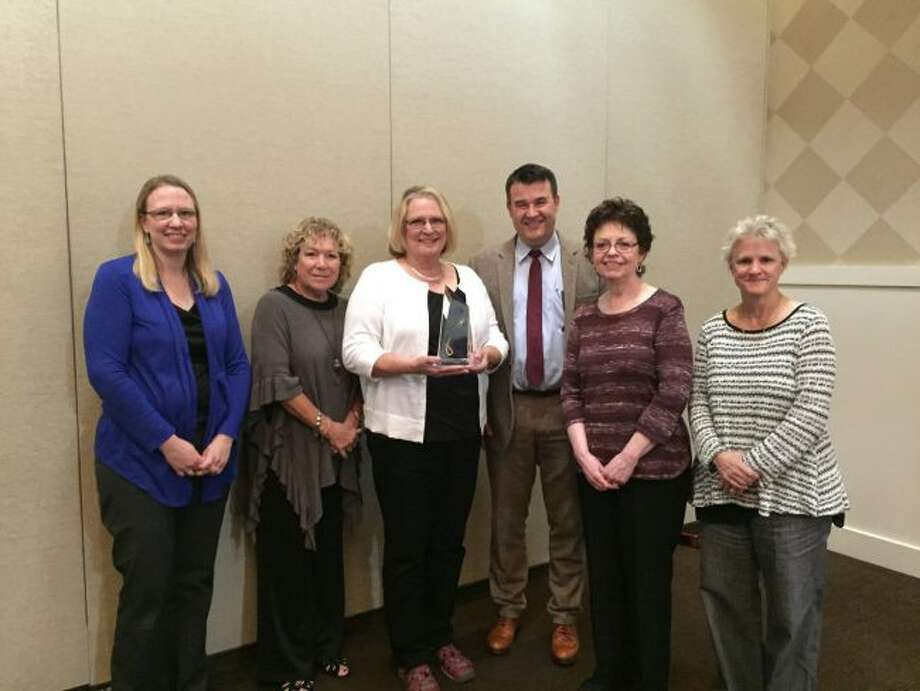 """Members of the Morton Township Library accept their Citation of Excellence trophy from Michigan State Librarian Randy Riley (third from the right) and previous Library of Michigan Foundation executive director Carolyn """"Sparky"""" Mowrey (second from left) during a recent luncheon in Novi. (Courtesy photo)"""