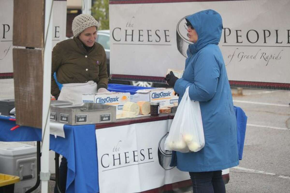 Mikayla Dlouhy (left) assists Lara Jaskiewicz at The Cheese People booth during the final farmers market on Friday. Dlouhy, who has been working at the market for approximately three years, said this season went well.