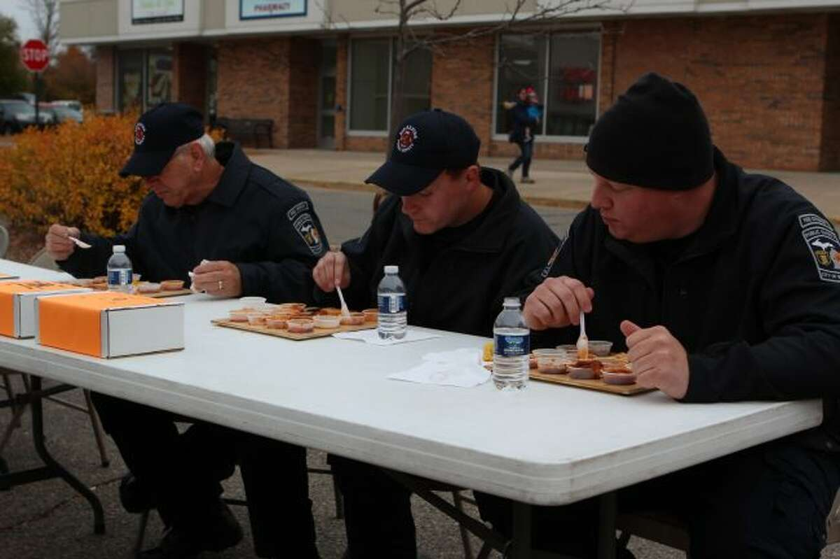 Big Rapids Department of Public Safety firefighters sample more than a dozen different chili recipes during Friday evening's chili cook-off, as part of the Downtown Business Authority's Fall Festival.
