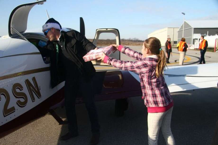 A pilot begins emptying presents from his plane at Roben-Hood Airport on Saturday for Operation Good Cheer.