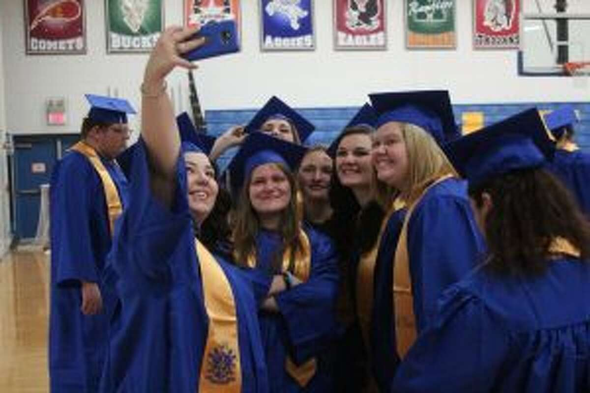 COMPLETION: Evart High School seniors take a moment for a selfie following Monday's tour of the district's schools. During the tour of the three schools, the soon-to-be graduates are greeted with cheers and applause from fellow students, teachers and administrators.
