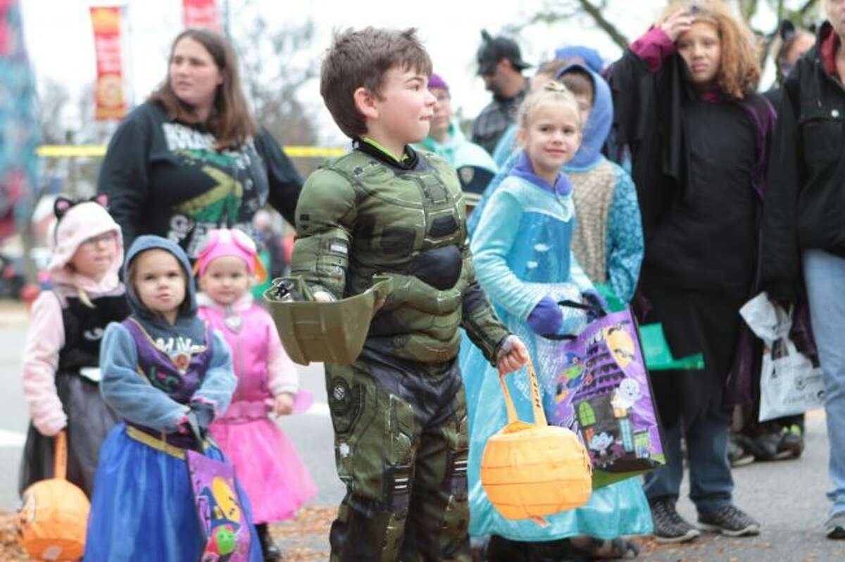 Children dressed up in their Halloween costumes line up to get candy during the trunk-or-treating Saturday morning in downtown Big Rapids, as part of the annual Fall Festival. There were several family-friendly events schedule Friday and Saturday for the annual event, hosted by the Big Rapids Downtown Business Association. (Pioneer photos/Brandon Fountain)