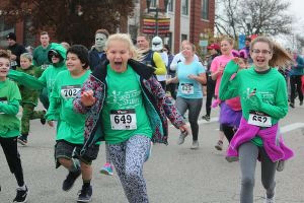 Whether dress up in costumes or sporting the coveted Skeleton Skurry shirt, runners shoot off the starting line during the sixth installment of the 5K run and walk Saturday morning in downtown Big Rapids.