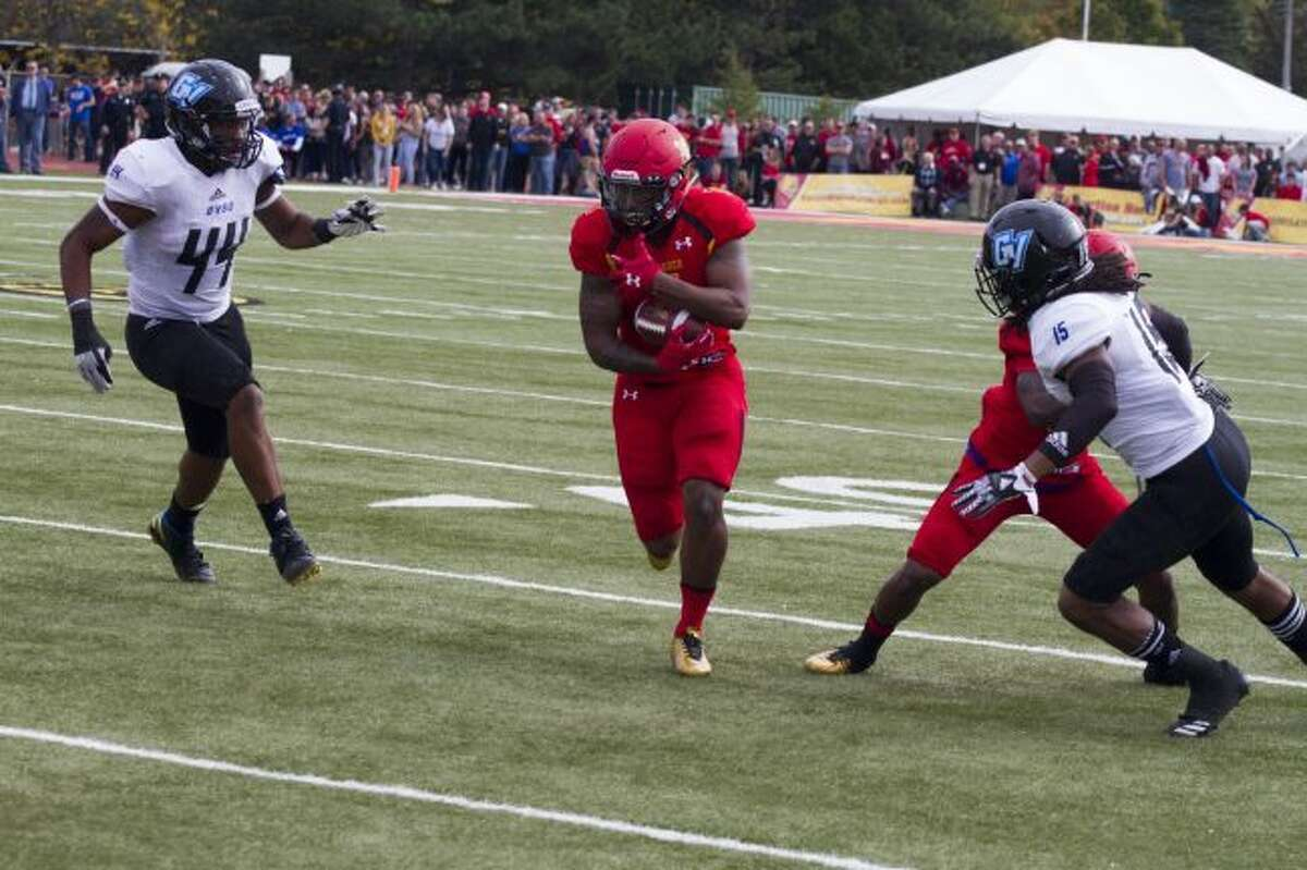 Ferris State back Robert Thomas III (1) finds a hole and runs past two Grand Valley defenders during Saturday's game at Top Taggart Field. (Pioneer photo/Maxwell Harden)