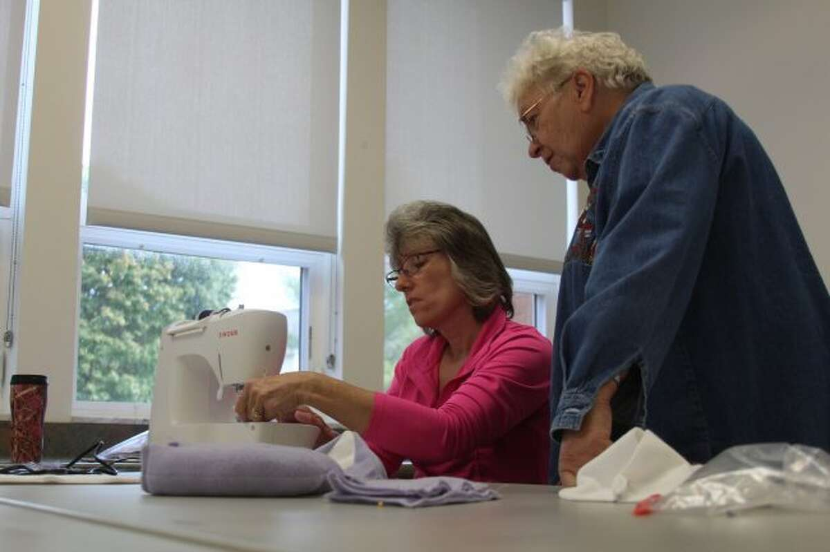 Carol Howe (right) looks on as Bunny Smith sews some of a Project Hero Hugs teddy bear together during a work session on Saturday at the West Campus Community Center on the campus of Ferris State University. The two are among many who have helped cut, sew, stitch and stuff teddy bears to be presented to veterans who return from a Mid-Michigan Honor Flight from Washington, D.C. (Pioneer photos/Brandon Fountain)