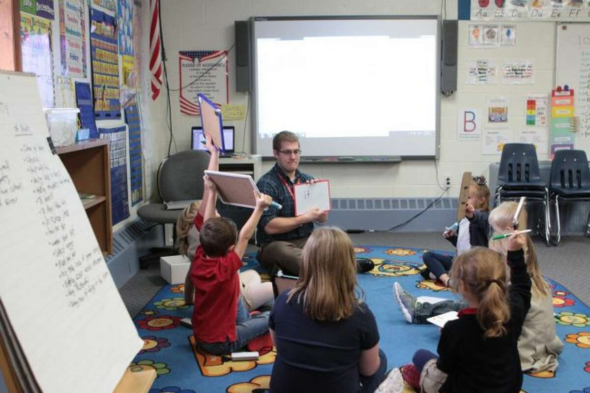 St. Michael Catholic School's new kindergarten teacher Jesse Olsen works on sight words with his class. During the lesson, students used whiteboards to practice writing different words, such as