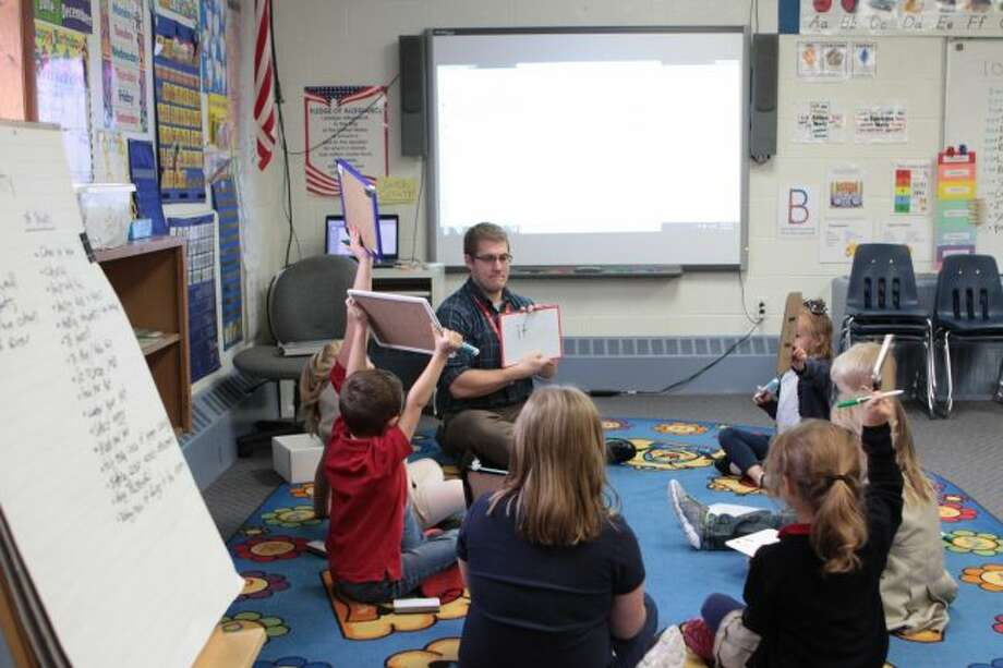 """St. Michael Catholic School's new kindergarten teacher Jesse Olsen works on sight words with his class. During the lesson, students used whiteboards to practice writing different words, such as """"it,"""" """"we,"""" """"the"""" and more. (Pioneer photo/Meghan Gunther-Haas)"""