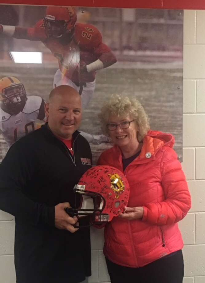 Dan Rohn, Ferris State University Quarterbacks Coach and Betty Seelye, Director of the United Way, stand together with a 2017 helmet signed by the 2017 Ferris football team. The helmet will be auctioned off at the United Way Auction on Thursday, Oct. 26. (Courtesy photo)