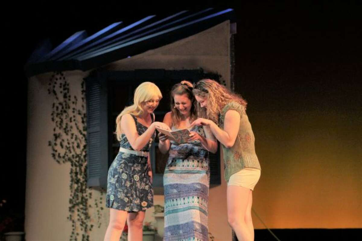 (From left) Nicola Hollinki, portraying Sophie; Leanna Kwilos, as Lisa; and Lilia Herdegen, playing Ali; look through a dairy during a dress rehearsal of