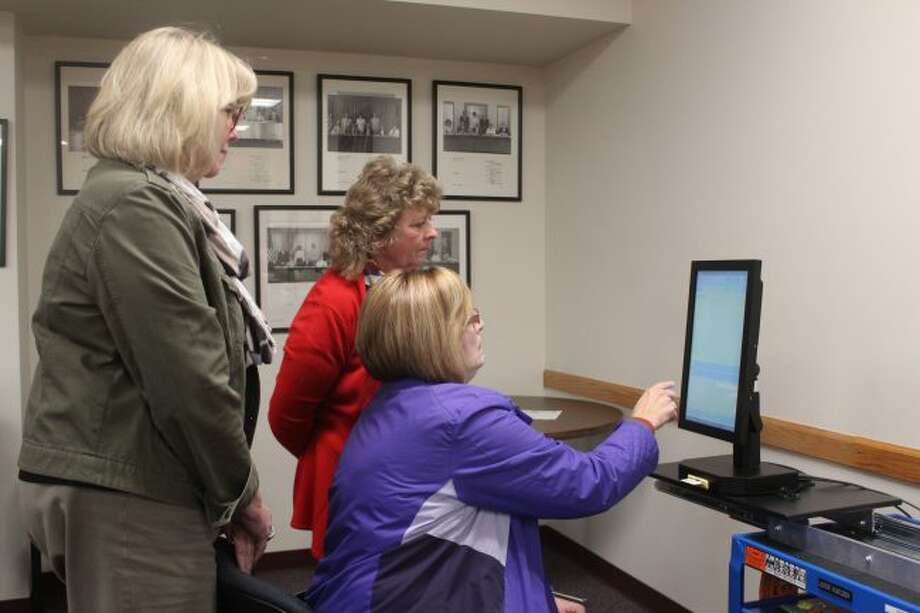 Cindy Plautz (left) and Paula Weipert (right) listen as Big Rapids City Clerk Tammy Gillis explains how the new handicap-accessible Dominion Voting election machine's touch screen works during Wednesday's open house at Big Rapids City Hall. (Pioneer photo/Brandon Fountain)
