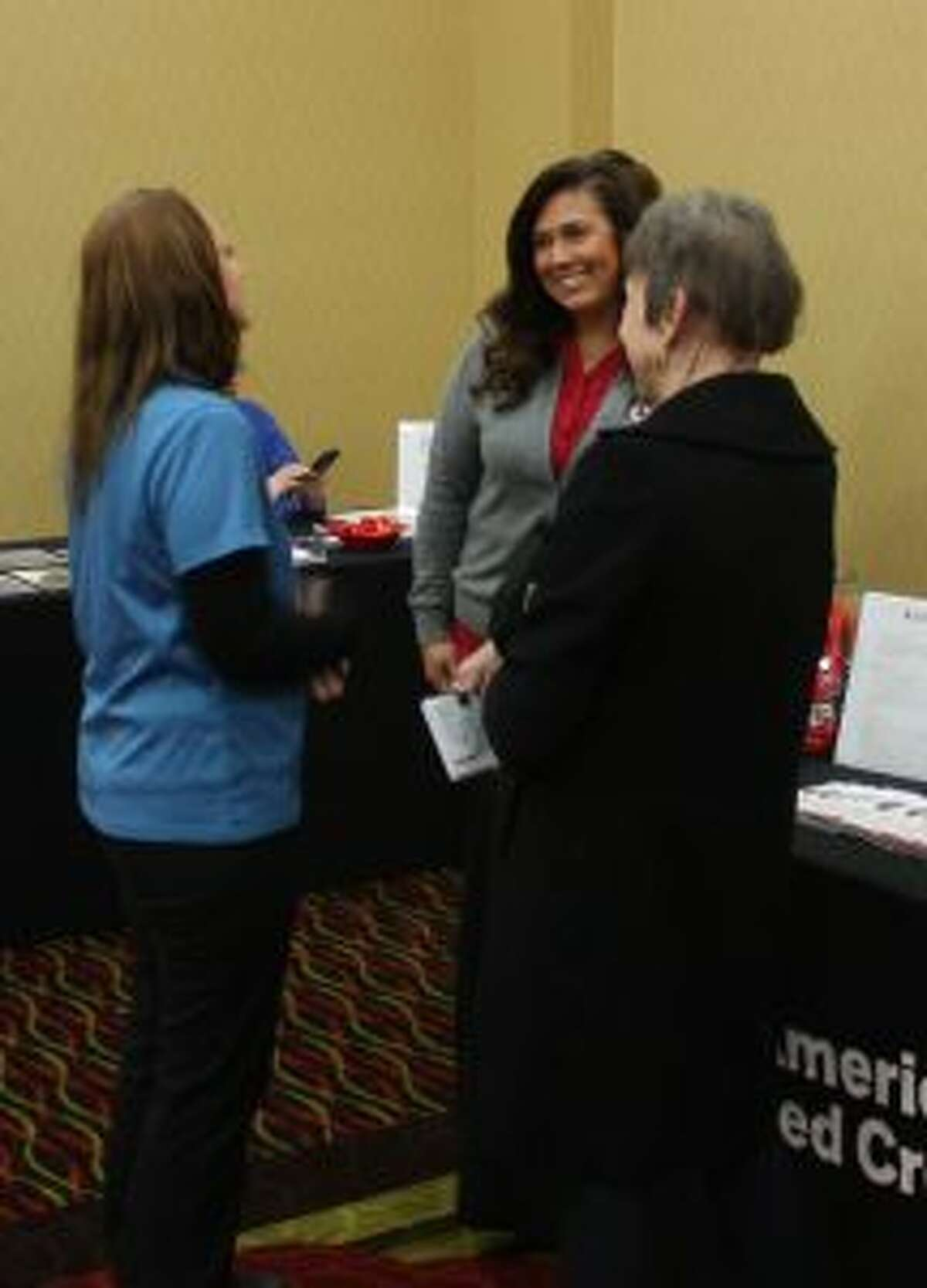 American Red Cross of West Michigan Executive Director Tiffany Page, second from left, is pictured speaking with Trisha Newcombe, far left, and Karen Shane at the Community Giving Day event Thursday. (Pioneer photo/Tim Rath)