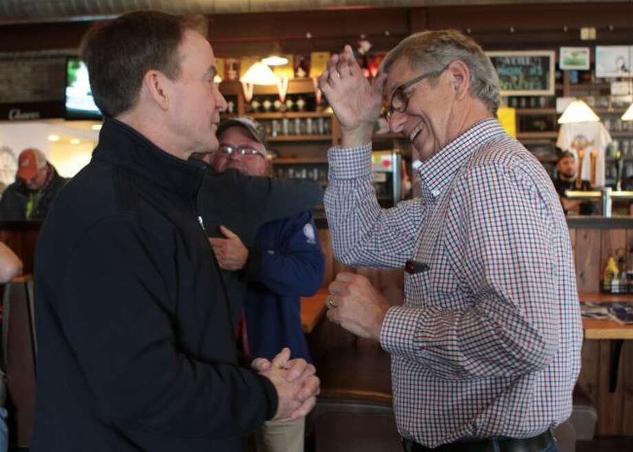 Bill Schuette (left), Republican candidate for governor of Michigan, and Ormand Hook, Mecosta County Republican Party chair, speak at Cranker's Brewery on Friday about encouraging constituents to vote in the general election on Tuesday, Nov. 6. (Pioneer photos/Taylor Fussman)