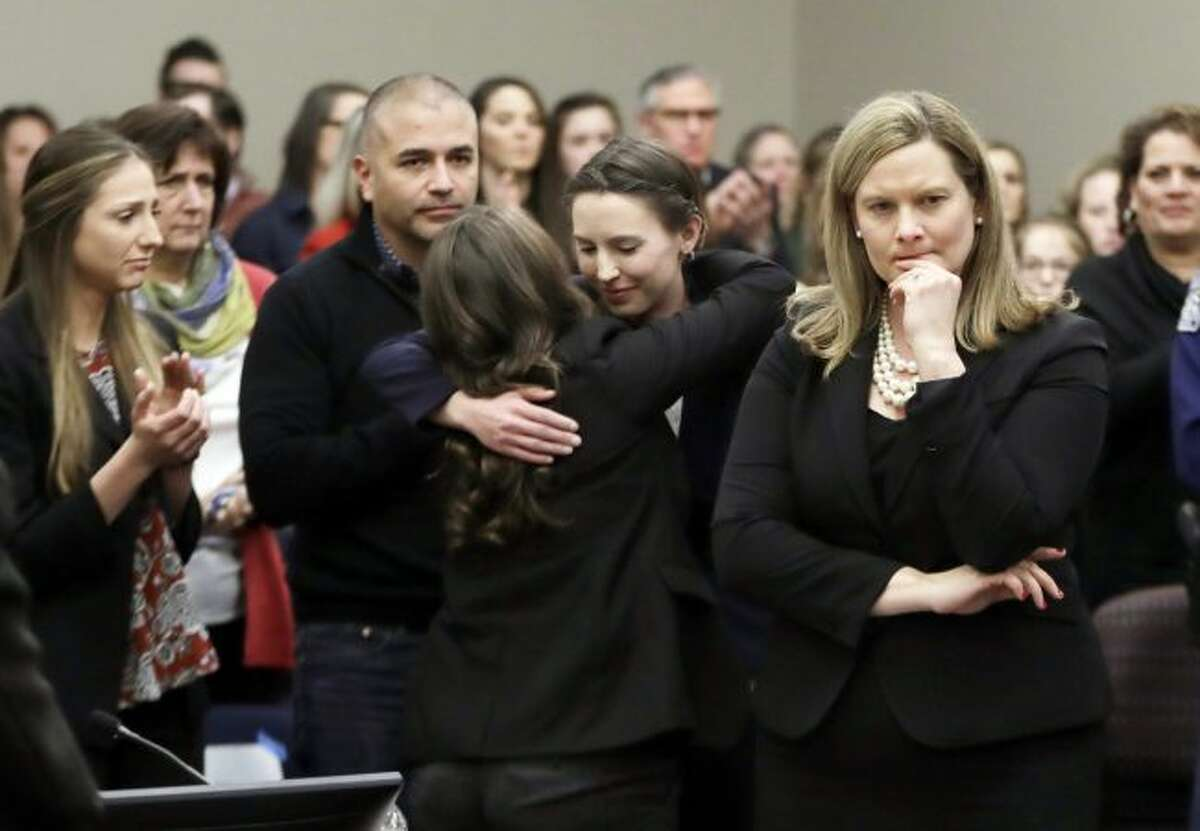 In this Jan. 24, 2018, file photo, former gymnast Rachael Denhollander, center, is hugged after giving her victim impact statement during the seventh day of Larry Nassar's sentencing hearing in Lansing, Mich. At right is Assistant Attorney General Angela Povilaitis. Michigan State University announced Wednesday, May 16, 2018, that it has reached a $500 million settlement with hundreds of women and girls who say they were sexually assaulted by sports Nassar in the worst sex-abuse case in sports history. (AP Photo/Carlos Osorio, File)