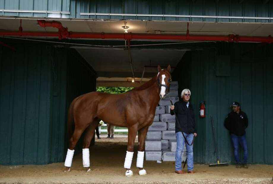 Trainer Bob Baffert walks Kentucky Derby winner Justify in a barn, Wednesday, May 16, 2018, after Justify's arrival at Pimlico Race Course in Baltimore. The Preakness Stakes horse race is scheduled to take place Saturday, May 19. (AP Photo/Patrick Semansky)