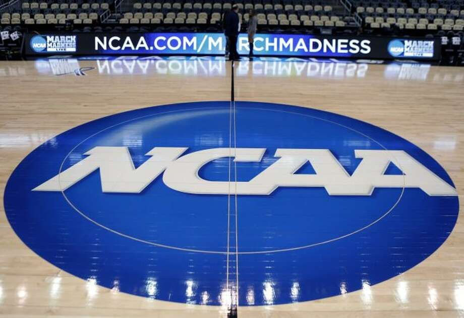 """In this March 18, 2015, file photo, the NCAA logo is displayed at center court as work continues at The Consol Energy Center in Pittsburgh, for the NCAA college basketball tournament. The NCAA is opening a door for states with legalized sports gambling to host NCAA championship events. The governing body for college sports on Thursday, May 17, 2018, announced a """"temporary"""" lifting of a ban that prevented events like college basketball's NCAA Tournament from being hosted in states that accept wagers on single games. (AP Photo/Keith Srakocic, File)"""