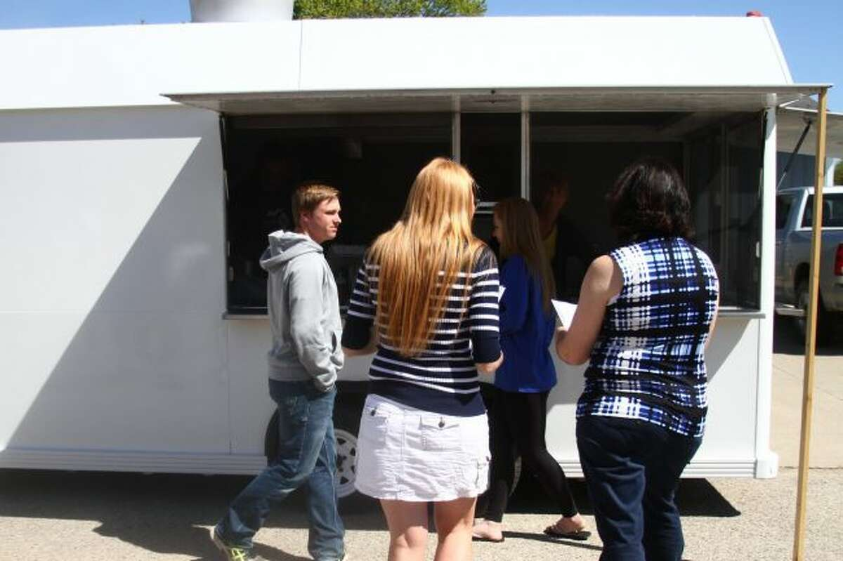 NEW LOOK COMING: Students and staff from Chippewa Hills High School wait to enjoy a meal from the Phat Matt food truck. The Phat Matt food truck is painted white and awaiting its new logo and wrap, which was designed by graphic design students from the high school.