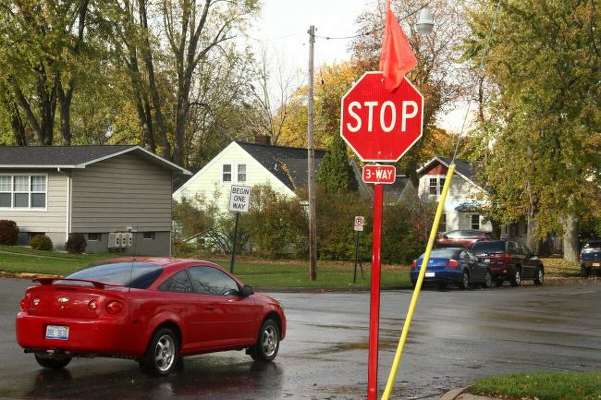A new stop sign on Ives Avenue near Oak Street is marked with an orange flag. The new stop sign was installed Friday to address increased traffic. (Pioneer photo/Emily Grove)