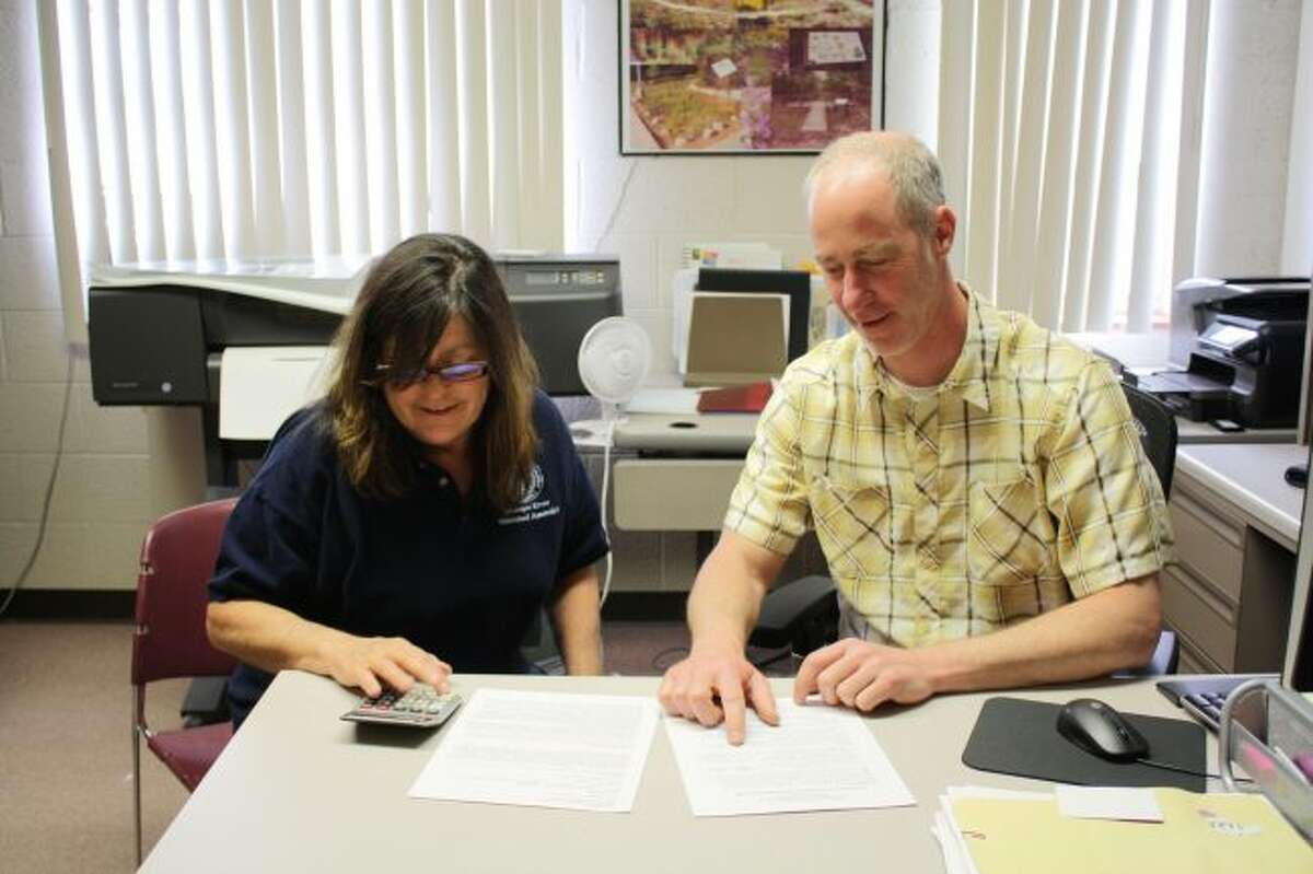 Patricia Jarrett (left), Muskegon River Watershed Authority office manager, and Marty Holtgren (right), MRWA executive director, go over a list of figures in Holtgren's office. (Pioneer photo/Candy Allan)