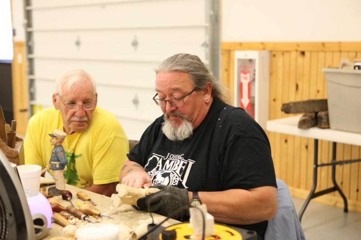 Floyd Rhadigan (right) helps Ron Brown carve some of the details of a marine figurine during the Spit and Whittle weekend at the Osceola County 4-H/FFA Fairgrounds in Evart. (Pioneer photos/Meghan Haas)