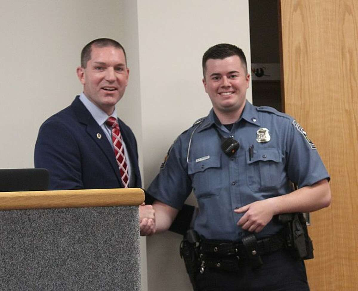 """Big Rapids Department of Public Safety Director Jim Eddinger (left) introduces the department's newest officer, Kasey Metcalf, to Big Rapids City Commissioners and city staff during Monday's meeting. Metcalf worked with DPS as a service officer from 2013 -15, while enrolled at Ferris State University, and graduated from Grand Rapids Community College. """"(Metcalf) is atypical of Millenials; he has shown a reverence to his position,"""" Eddinger said. (Pioneer photo/Brandon Fountain)"""