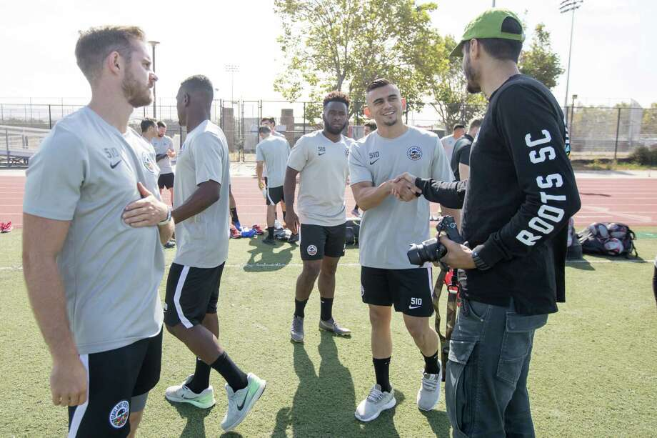 Oakland Roots player Angel Heredia shakes hands with Edreece Arghandiwal (back to camera) before their first ever practice at the College of Alameda on July 25, 2019. Photo: Douglas Zimmerman, SFGate