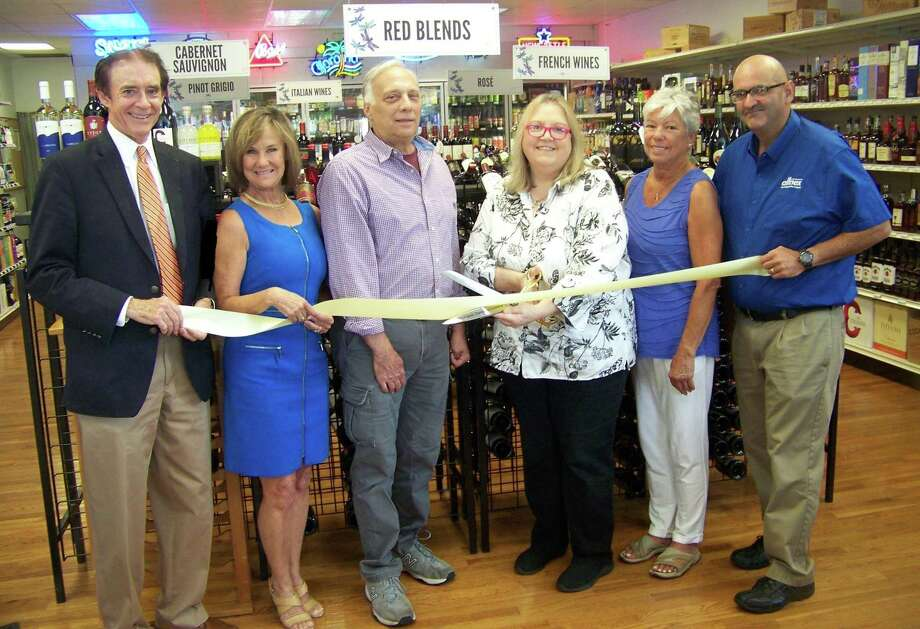"""From left, Wallingford Mayor William Dickinson; Quinnipiac Chamber of Commerce Executive Director Dee Prior-Nesti; Robert Scagnelli; owner Brenda Robideau; Mary Cortese; and Quinnipiac Chamber of Commerce board chairman Frank DiCristina celebrate the ribbon-cutting for Dragonfly Wine & Spirts, 382 Center St. in Wallingford. """"Dragonflies represent transformation and are considered a good luck charm, so it was a perfect fit for the transformation of our store,"""" Robideau said in a relase. """"It is important for us to be here for the neighborhood patrons as well as for the people who are visiting Wallingford."""" The store focuses on hand-selected wines as well as everyday favorites, craft and local beer, bourbon and more, and holds weekly wine tastings on Friday evenings. Photo: Contributed Photo"""