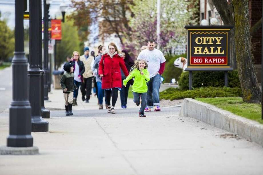 Passing Big Rapids City Hall, walkers head down Michigan Avenue during a previous Walk a Mile event for WISE during Sexual Assault Awareness Month. This year's event is set for Saturday, April 21. The walk aims to raise awareness about sexual harassment and the scope of sexual violence on campus. (Pioneer file photo)