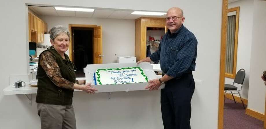 After more than 40 years, Bruce Cummings (right) will be retiring from the Martiny Township board. To celebrate his years of service, a surprise party was planned following his final board meeting as supervisor. (Pictured) Cummings holds the cake prepared for his party with his wife, Marlene (left). (Pioneer photos/Meghan Gunther-Haas)
