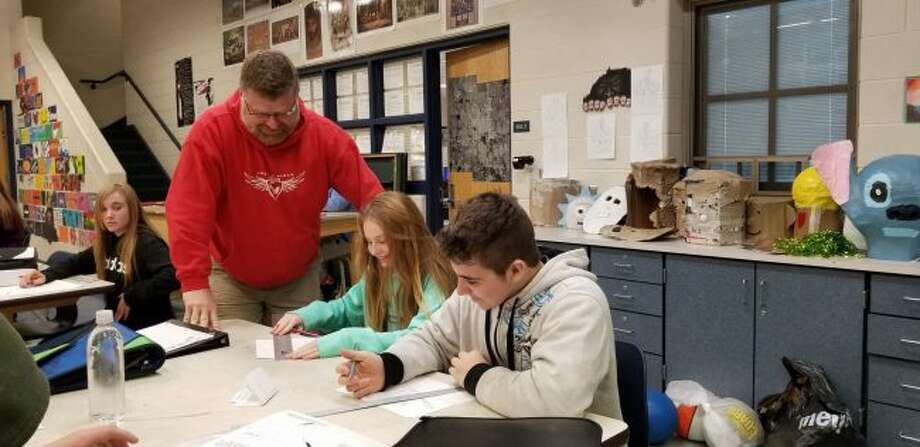 Chippewa Hills Intermediate School art teacher works with students on an assignment. When not in the classroom, O'Neil drives a bus, coaches cross country, maintains the cross country courses, assists with maintenance of the grounds and more. (Pioneer photo/Meghan Gunther-Haas)