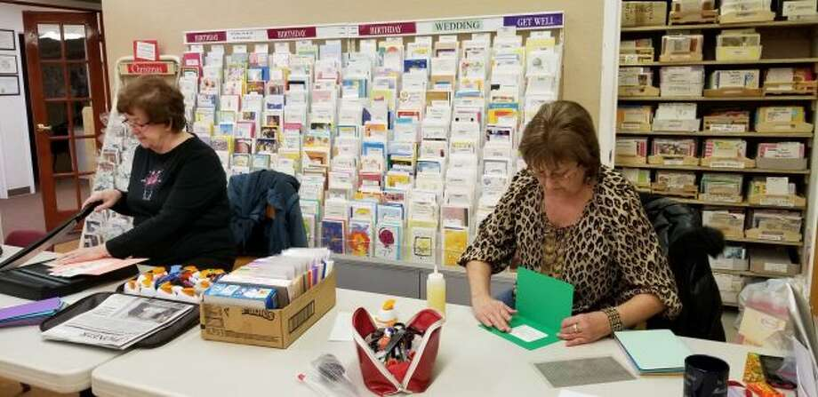 Chris Miller (right) and Jan Keelor work together to recycle new and used cards, which will later be sold at the Mecosta County Commission on Aging senior center. Miller said volunteers are always welcome to join to Tuesday and Friday program. (Pioneer photo/Meghan Gunther-Haas)