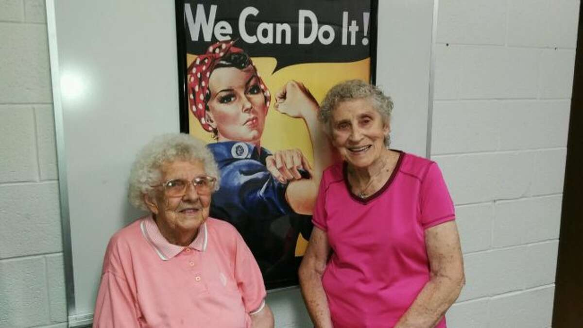Evelyn Dunn (left) and Fran Brackett (right) walk inside Big Rapids Middle School for exercise. They posed for a photo in front of a reprint of a World War II poster of Rosie the Riveter. (Courtesy photo)