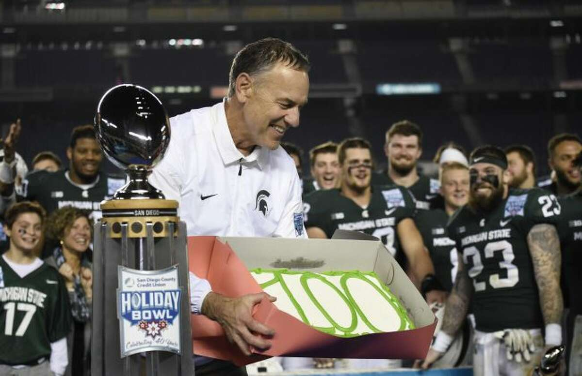 """Michigan State coach Mark Dantonio holds a cake with """"100"""" written on it after Michigan State defeated Washington State 42-17 in the Holiday Bowl NCAA college football game Thursday, Dec. 28, 2017, in San Diego. It was Dantonio's 100th win to close his 11th season and his school-record fifth bowl. (AP Photo/Denis Poroy)"""